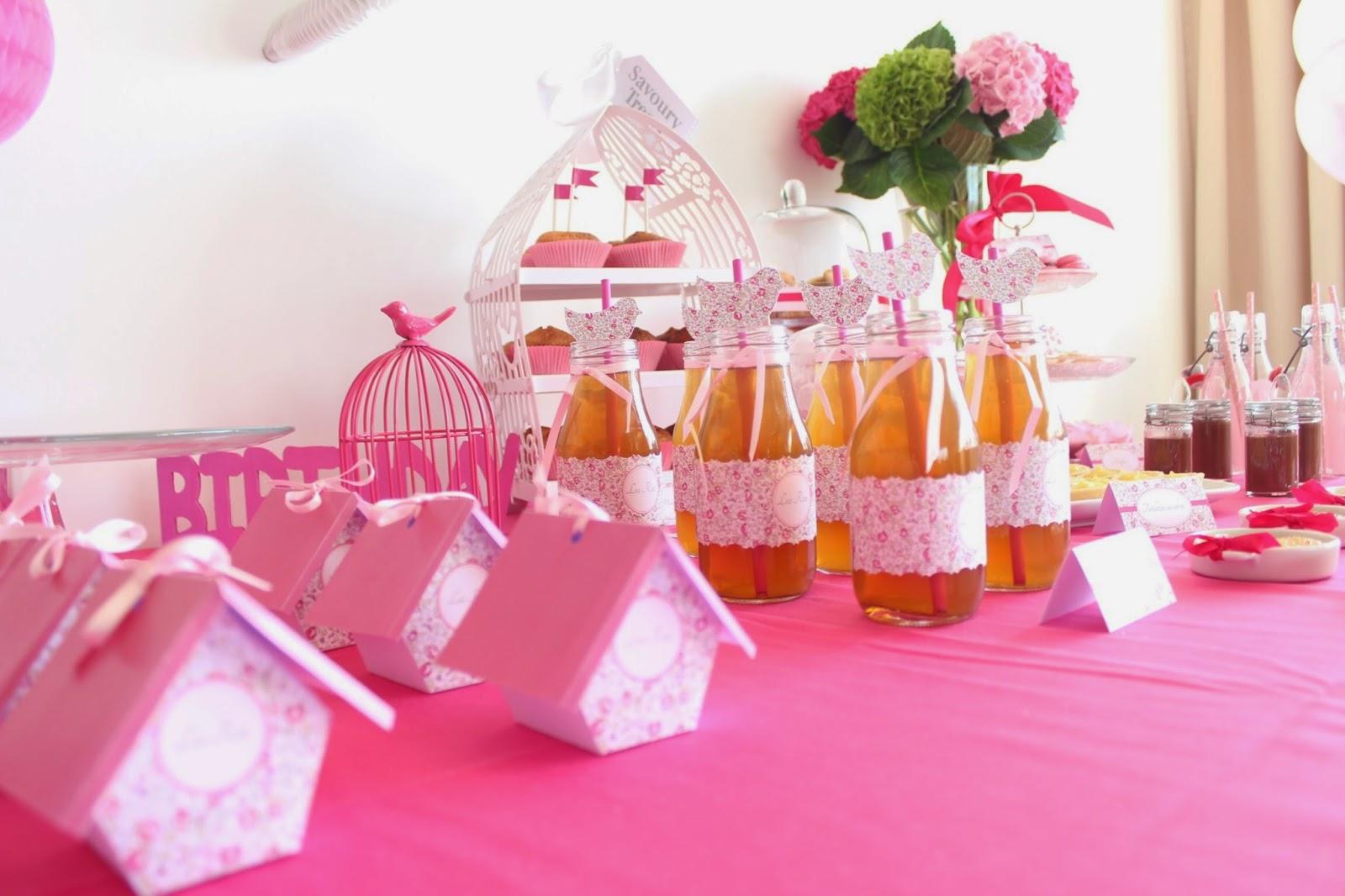 table d'anniversaire decoree de bouteilles et de mini cages roses pour bonbons