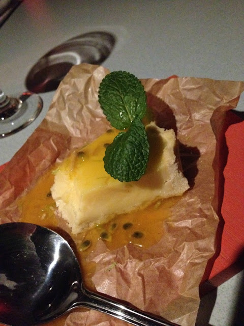 lemon and lime tart with sprig of mint and passion fruit sauce on paper on a board