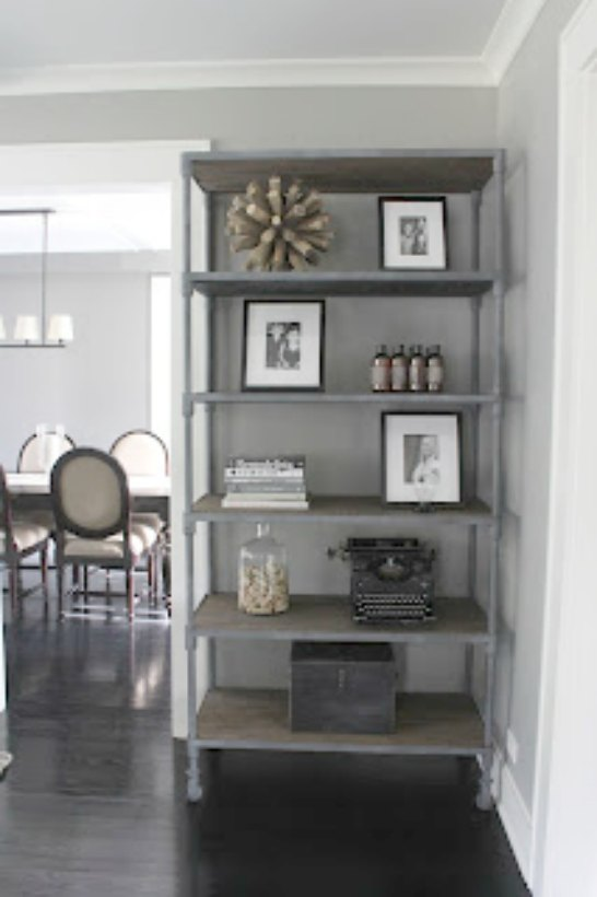 Reclaimed distressed wood etagere shelving in modern farmhouse living room on Hello Lovely Studio