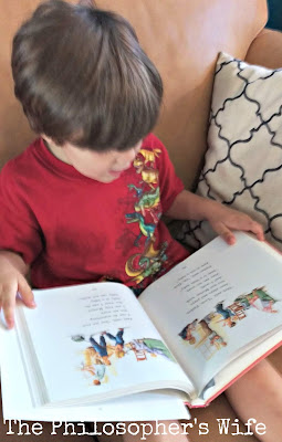 A young boy, wearing a red shirt with dinosaurs, is reading a picture book called Dick and Jane.
