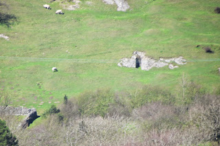 A zoom picture of one of the limestone scars with what appears to be the entrance to a cave.