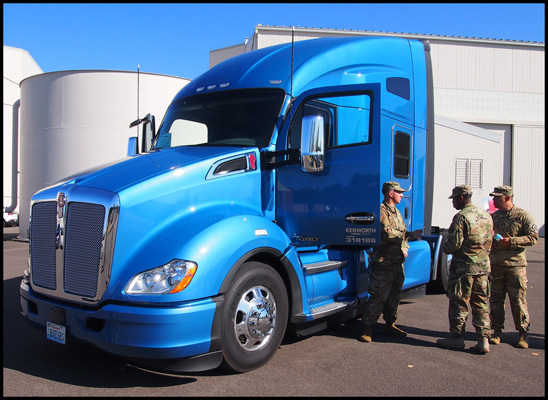 US Military Members pose for a photo with a Kenworth T680
