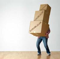 Üzerinde sorumluluk yazan üç büyük ve ağır kutuyu kucağında taşırken arkasında kaybolup görünmeyen bir adam
