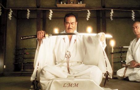 """Cette image est extraite du film """"Kill Bill"""" que Quentin Tarantino a realise en 2003. Elle montre un homme d'origine asiatique tout de blanc vetu, assis en position du lotus, en train de tendre à bout de bras une epee legerement courbee, un katant. Cet homme est l'acteur Sonny chiba, qui incarne Hattori Hanzo dans le film, un celebre forgeron a la retraite, que La Mariee laissee pour morte lors de son mariage par ses anciens partenaires de l'organisation de tueurs a gage Le Detachement International des Viperes Assassines, vient voir a Okinawa afin qu'il lui forge un katana exceptionnel qui sera l'arme de sa vengeance. Cette image accompagne le poeme u Marginal Magnifique dans lequel l'immense poete affirme sa volonte d'affronter sans sourciller les vicissitudes de ce monde. Sonny chiba, celebre acteur asiatique de films d'arts martiaux a ete choisi pour illustrer cette force de caractere et son personnage d'Hattori Hanzo represente quant a lui la dignite et la noblesse, le refus des compromissions, puisqu'il a choisi de se retirer pour ne pas creer d'armes de mort, abandonnant du meme coup honneurs et fortune. Encore un extraordinaire poeme du Marginal Magnifique !"""