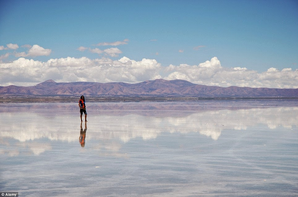 This tourist is enjoying herself in this fantastic dreamscape of the Uyuni salt flats. - A Hidden Place That Looks Like Heaven… Where The Ocean Meets The Sky.