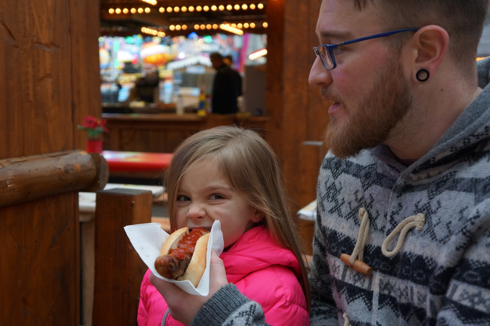 little girl eating a sausage at london winter wonderland