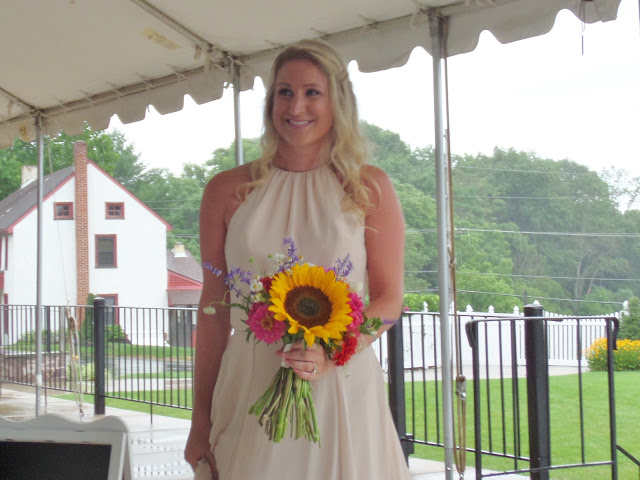 beige bridesmaid dress with sunflower bouquet