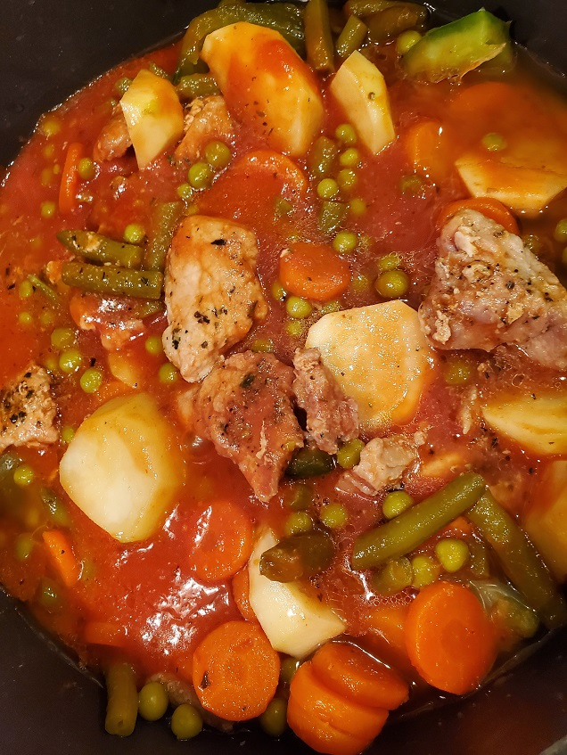 this is soup pot of stew with pork, peas, carrots and green beans with potatoes and tomato sauce