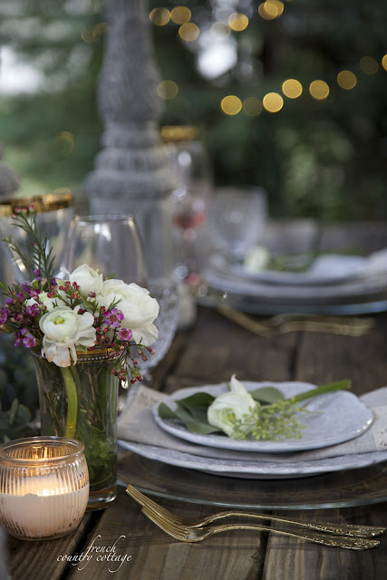 Table setting close up with flowers and gold flatware