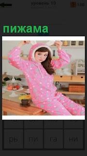 На столе на кухне сидит девочка в розовой пижаме с ушками на голове