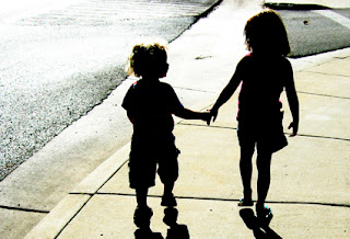 Siblings of Kids with Autism Holding Hands Walking Down the Sidewalk