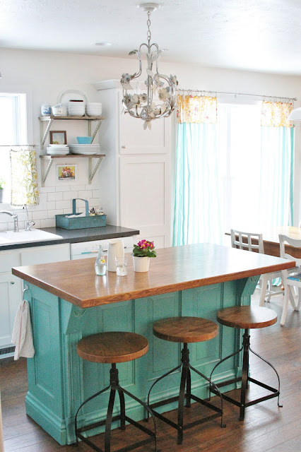 A white rustic kitchen with a chandelier above a turquoise island with a wooden top.