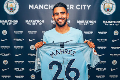 Riyad Mahrez poses with Manchester city shirt after completing transfer