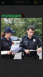 полицейские в форме составляют протокол на улице