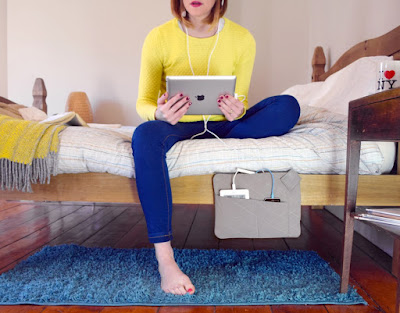 woman sitting on a bed that has a bedside pocket that holds products being charged