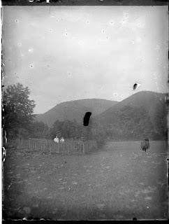 Zwei Personen im Garten vor einer Hügellandschaft - um 1900