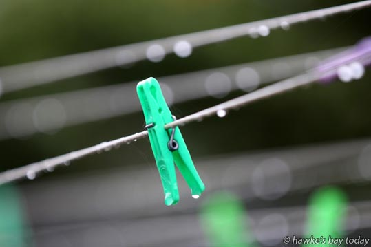 Wet pegs on a wet washing line - wet weather, rain forecast for the rest of the week. photograph