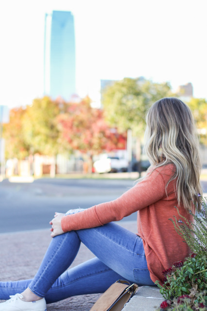 blonde girl gazing towards devon tower in oklahoma city