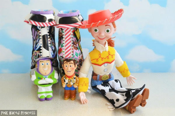 ankle boots side by side with heels facing outwards with Buzz and Woody character heels and large Jessie doll sitting beside and sky background