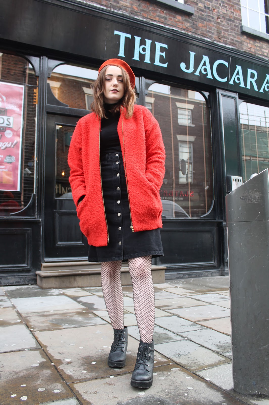 60s inspired outfit including orange Mary Quant beret, black polo neck jumper, black denim button up midi skirt, orange boucle pea coat, fishnet tights and black lace up boots