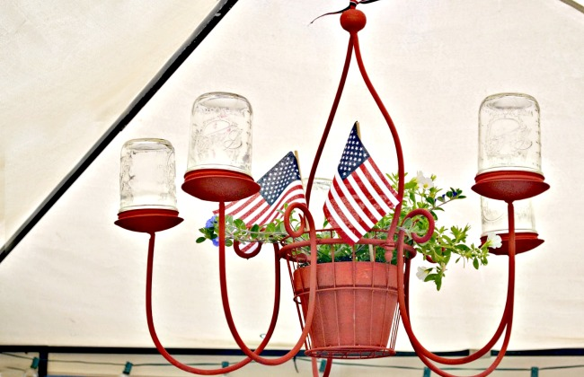 red chandelier with mason jars and a plant with flags
