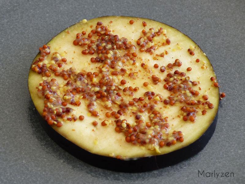 Etalez une couche de moutarde à l'ancienne sur une tranche d'aubergine.
