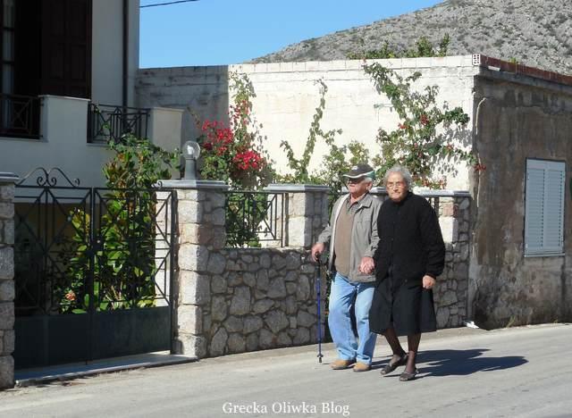 ubrana na czarno babcia trzyma za rękę dziadka podpierającego się laską