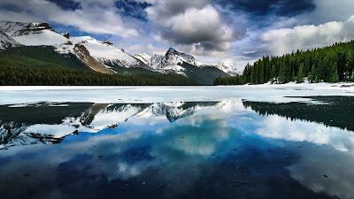 Impresionante paisaje de lago congelado con montañas y arboles de fondo