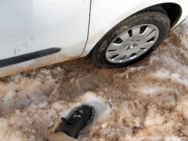 Van's right passenger tire is in deep snow, partially dug out and filled with brown gravel near Coyote Hollow Equestrian Campground in Dixie National Forest, Utah. A sandaled foot with sock is shown.