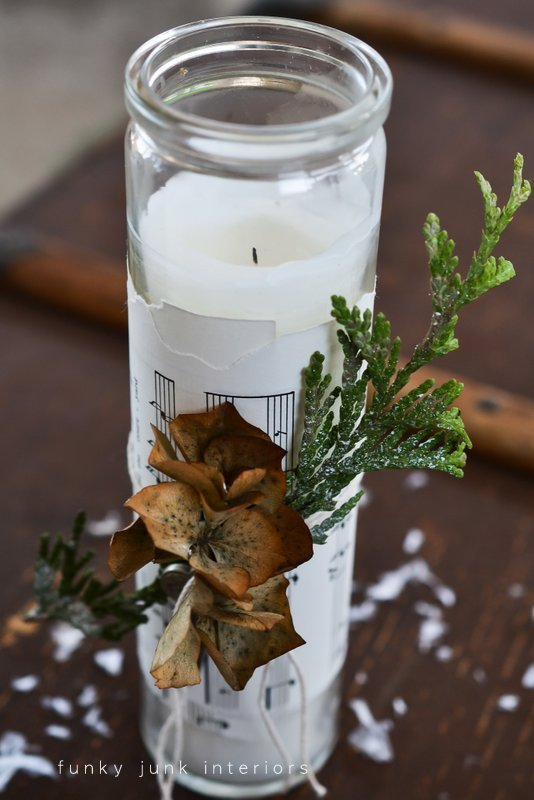 candle wrapped with greens, hydrangeas and key