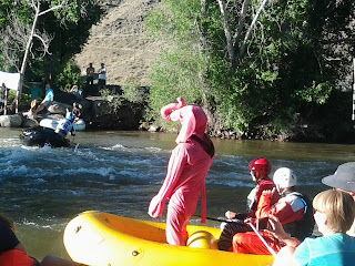 River competition with a person dressed in a pink elephant standing in the raft watching the other rafts, spectator all around.