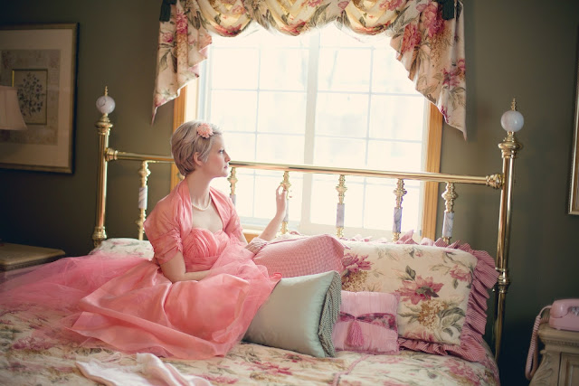 Woman in Pink Sitting Up in Bed, Light Pouring Into Room