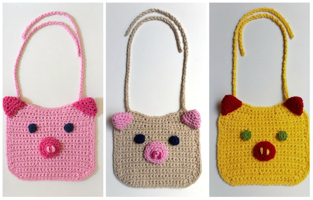 Three little bibs in a row. They are shaped like squares with rounded corners. On the top corners are triangular ears that stick out. The eyes and snout are appliqued onto the bib. The snout has two nostrils made from embroidery - just two simple stitches.  Each bib is its own colour. 1: pale pink bib & ties, dark pink ears and nose, pink nostrils, blue eyes. 2. Fawn bib & ties, pale pink ears and nose, dark pink nostrils, blue eyes. 3. Yellow bib and ties, red ears and nose, yellow nostrils, green eyes.