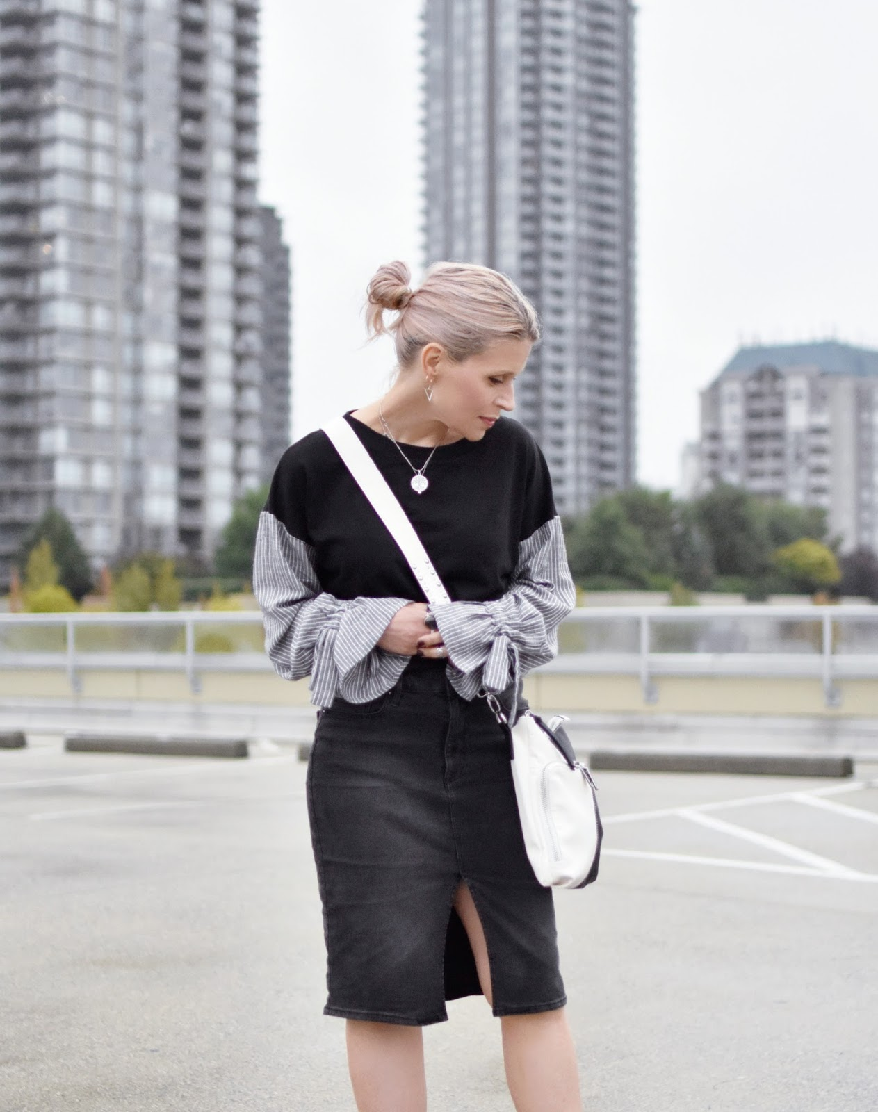 Monika Faulkner outfit inspiration - black sweatshirt with mixed media sleeves, black denim skirt, black and white cross-body bag