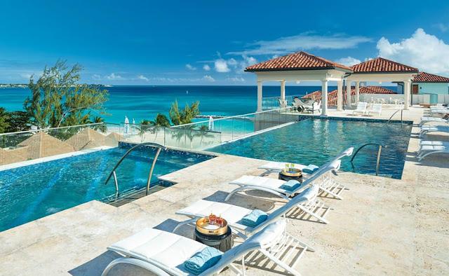 Chaise longue, bain de soleil face à la piscine débordante et vue sur la mer des Caraibes