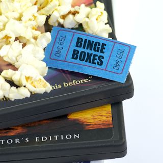 "dvds, popcorn, and movie ticket that says ""binge boxes"""