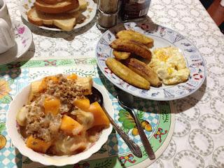 "left: papaya, banana, and ""badea"" with yogurt & granola; right: fried plantains and eggs"