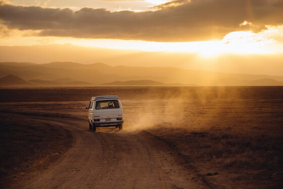 Vanagon on a lonely stretch of desert dirt road, sunset coming