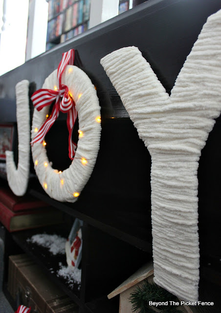 joy sign, Christmas craft, chenille yarn, twinkle lights, hot glue, http://www.beyondthepicket-fence.com/2016/12/12-days-of-christmas-day-11-warm-and.html