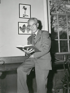 A black and white photograph of an older man in a suit, leaning against a desk with an open book in his hand.