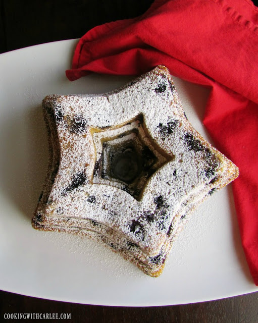 star shaped bundt cake with blueberries in the cake and powdered sugar on top