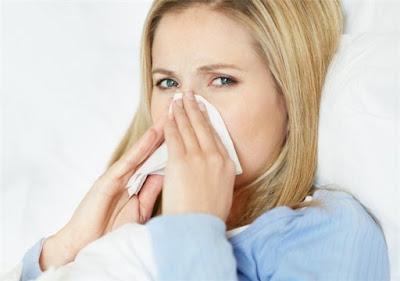 Una joven mujer con gripe acostada en la cama