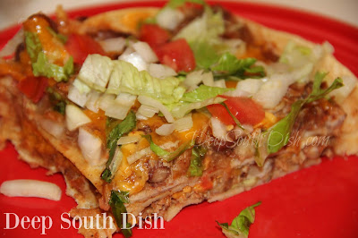 A Tex-Mex casserole made from seasoned shredded pork, chicken or beef and beans, layered with corn tortillas, cheese and taco sauce and finished with chopped onion, tomato and shredded lettuce.