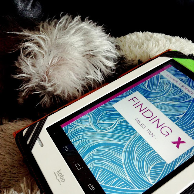 A fuzzy grey poodle, Murchie, curls up beside a white Kobo so only the top of his silver head and a flash of his darker muzzle are visible. The Kobo's screen holds the cover of Finding X, which features the title in fuscia over drawn swirls of blue hair.