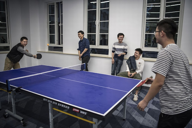 Huawei workers play table tennis in an employee leisure area at the Ox Horn Research and Development campus