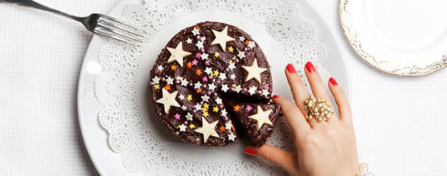 κεικ τούρτα με χρωματιστά αστέρια σε διάφορα μεγέθη και χρώματα με γυναικείο χέρι με δαχτυλίδι χρυσό και κόκκινα νύχια παίρνει τριγωνικό κομμένο κομμάτι σε άπρο πιάτο και πιρούνι