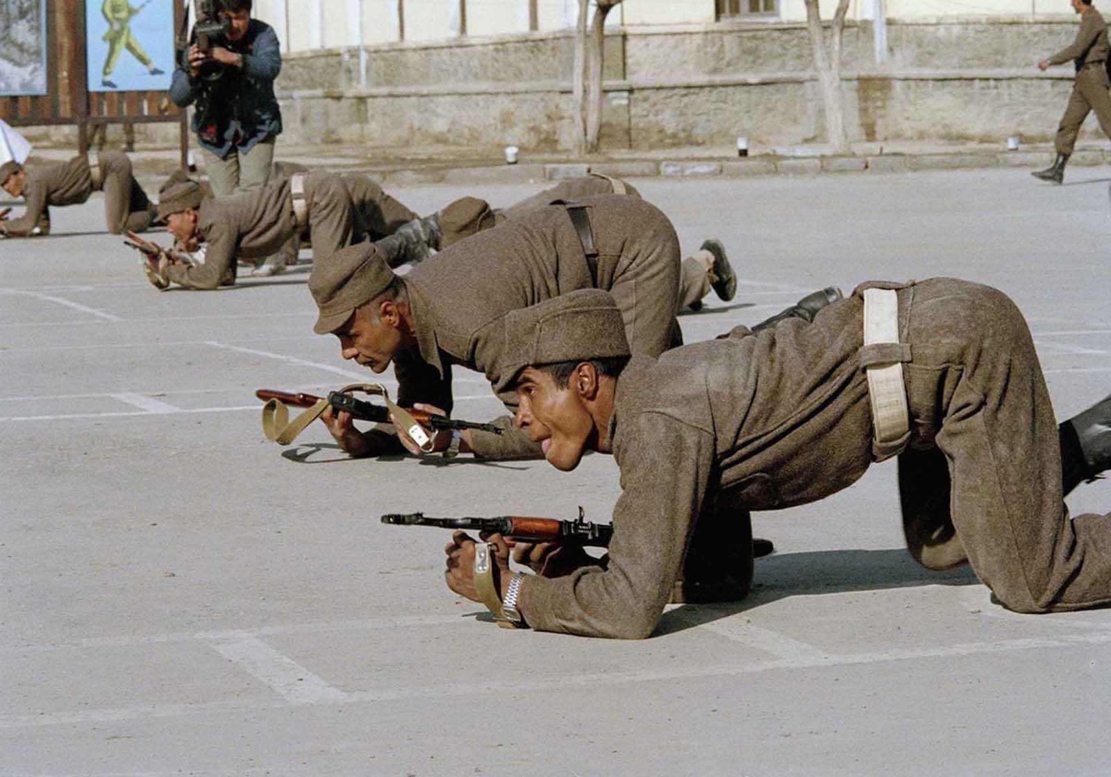 As the planned withdrawal of Soviet troops began, Afghan troops were trained and supplied to take their place. Here, a soldier crawls with his comrades, during a training session in Kabul on February 8, 1989. According to officials, the soldiers were from a new unit formed to defend vital installations in the Afghan capital.