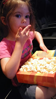 youngest at cinema with popcorn