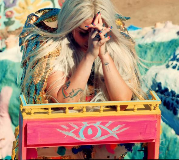 Kesha rezando sobre un altar con el ojo illuminati en su video Praying