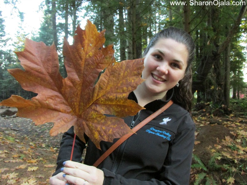 girl holding large maple leaf